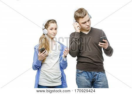 Beautiful teen age boy and girl in casual clothes standing on white background listening to music in headphones. School children. Isolated. Copy space.