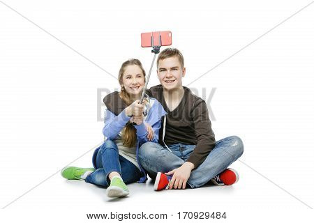 Beautiful teen age boy and girl in casual clothes taking selfie photo using mobile phone with stick. School children isolated on white background. Copy space.