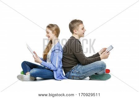 Beautiful teen age boy and girl in casual clothes holding tablets. School children sitting back to back. Isolated on white background. Copy space.