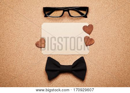 Spectacles, bowtie and empty paper blank in Happy Fathers Day. Cork board background top view, flat lay.