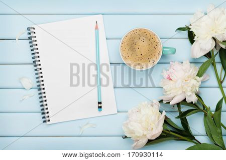 Morning coffee mug, empty notebook, pencil, glasses and white peony flowers on blue wooden table. Cozy summer breakfast top view, flat lay.