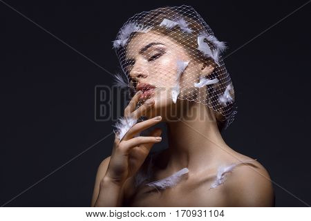 Portret of beautiful young woman with natural makeup. Face covered in veil net with white feathers on it. Hands with beige nude manicure. Studio shot on black background. Copy space.