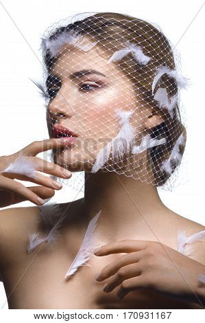 Portret of beautiful young woman with natural makeup. Face covered in veil net with white feathers on it. Hands with beige nude manicure. Studio shot isolated on white background. Copy space.
