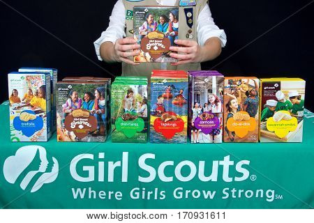 Alameda CA - February 12 2017: Traditional Girl Scout cookie booth with Little Brownie Baker brand cookies with a black background. Cadette Girl Scout holding up box of newest brand S'more cookies.