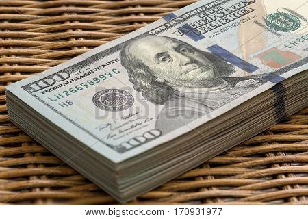 Stack of United States of America USD 100 One Hundred Dollars Federal Reserve Note in a Pile on Wicker Background