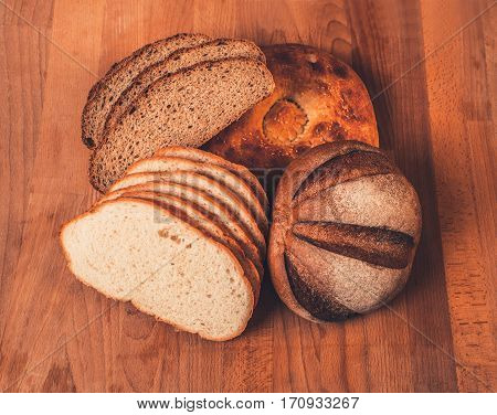 Assorted white and rye bread on a wooden table. Top view. Fresh fragrant crispy sliced bread. Loaf of white and rye bread slices on cutting board closeup. Home-made bread on a wooden background.