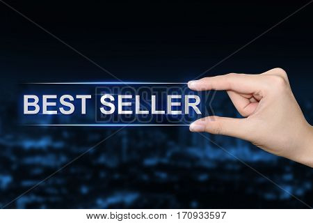 hand pushing best seller button on blurred blue background
