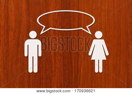 Paper man and woman is talking on wooden background. Dialog or conversation. Abstract conceptual image
