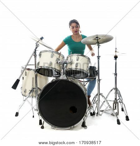 brunette brazilian woman concentrates on playing the drums in studio against white background