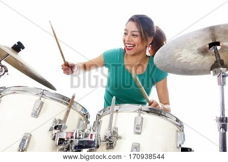 brunette brazilian woman has fun playing the drums in studio against white background
