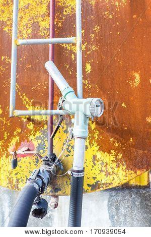 Old Rustic Pump On Grunge Metal Tank