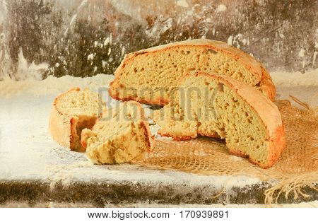 Freshly baked traditional bread on wooden table. Retro bread on the background of the table with flour. White whole grain loaves composition with wheat flour sprinkled around.