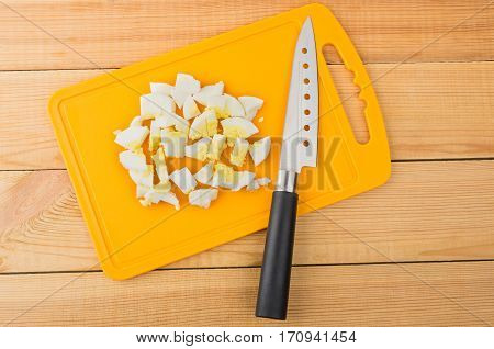 Chopped Boiled Egg And Knife On Plastic Chopping Board
