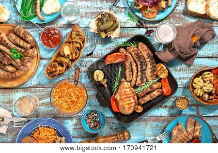 Variety of food grilled on wooden table top view. Outdoors food Concept