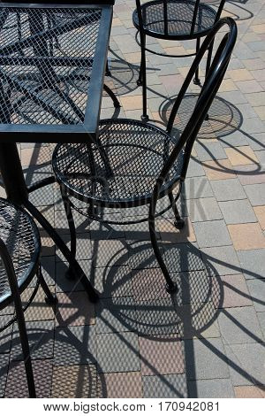 Several black mesh chairs and a table casting shadows on a tiled courtyard