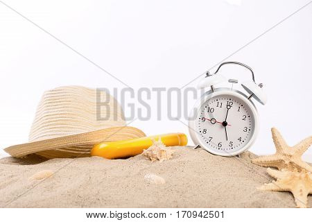 White vintage alarm clock straw hat suntan lotion and starfish on the sand on a white background