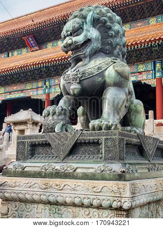 Beijing, China - Oct 30, 2016: Bronze lion with right paw on globe symbolizes projection of world-wide imperial power. At Gate of Supreme Harmony (Taihemen), Forbidden City (Gu Gong, Palace Museum).