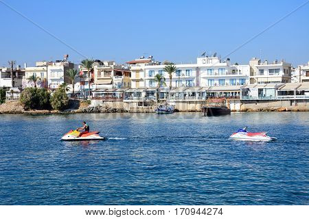 HERSONISSOS, CRETE - SEPTEMBER 17, 2016 - Man riding a jetski in the harbour with views towards waterfront restaurants Hersonissos Crete Greece Europe, September 17, 2016.