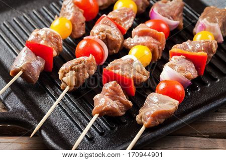 Raw Turkey Meat Skewers With Cherry Tomatoes, Pepper And Onion On Grill