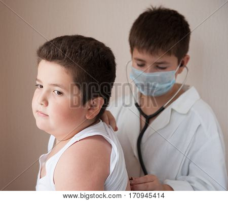 boy in the mask and white costume of the doctor listens to the heart rate of fat boy