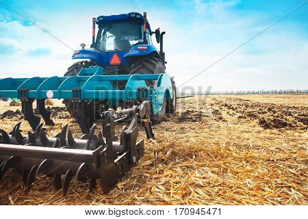 Modern tractor in a field on a sunny day.. The concept of work in a fields and agriculture industry.