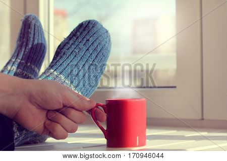 feet in warm socks and a mug with a hot drink on the table in front of window / warming atmosphere of home holiday