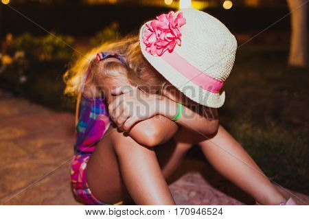 Portrait of sad resentful little girl sitting on the ground at the night time.