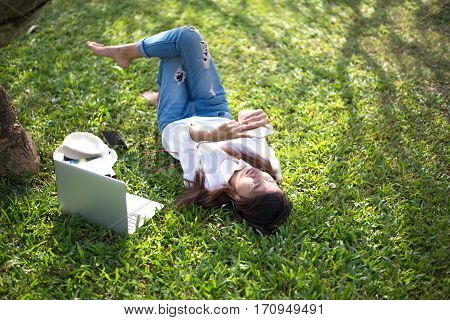 Girl enjoy listening music and reading a book and play laptop on the grass field of the park in the morning (greenery tone)