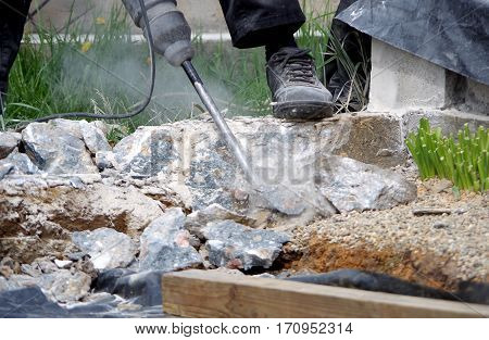 Worker removes old concrete with a jackhammer