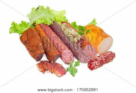 Partly sliced two pieces of the dried pork tenderloin different varieties of cooked smoked and dry smoked sausages salami ham with turkeys parsley and lettuce on a light background