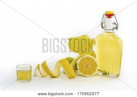 Open glass decanter bottle and shot glass filled with yellow lemon liquor or limoncello or limoncino on white. Peeled natural organic lemon.