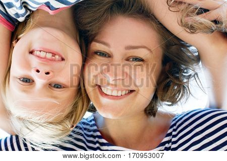 Laughing young mother and her little daughter outdoors in the summer sunshine with the breeze blowing their long blonde hair close up shot