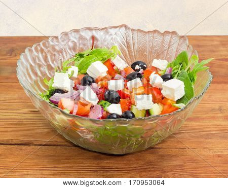 Greek salad in a glass salad bowl on an old wooden surface