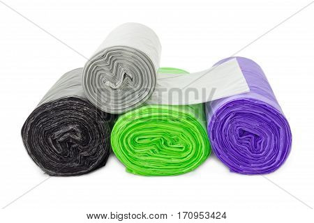 Several plastic disposable garbage bags of different sizes and colors in rolls including biodegradable closeup on a light background