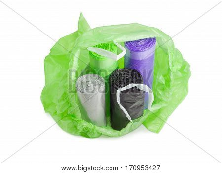 Several plastic disposable garbage bags of different sizes and colors in rolls in an open one of them with handles made from ribbons which may be tied on a light background