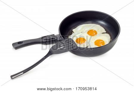 Three freshly fried eggs prepared with unbroken yolk in the frying pan and the black plastic spatula on a light background