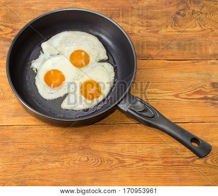 Three freshly fried eggs prepared with unbroken yolk in the frying pan on a surface of an old wooden planks