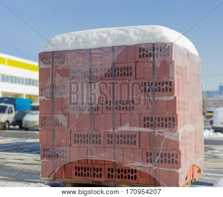 Red perforated bricks packed on a wooden pallet with plastic wrap and covered snow on an outdoor warehouse in winter sunny day