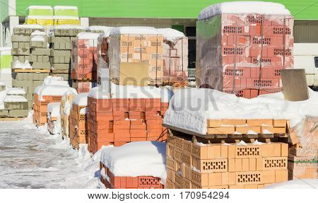 Pallets with different red bricks and concrete masonry units covered snow on an outdoor warehouse in winter sunny day