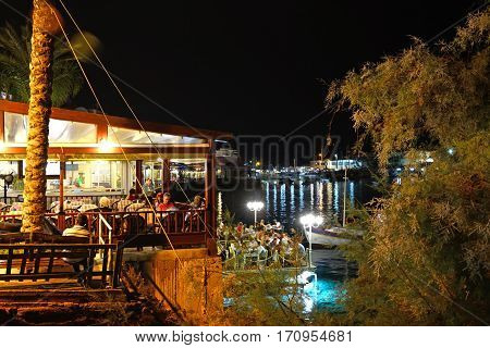 HERSONISSOS, CRETE - SEPTEMBER 18, 2016 - Waterfront restaurants with views across the harbour at night Hersonissos Crete Greece Europe, September 18, 2016.