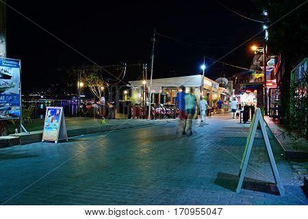 HERSONISSOS, CRETE - SEPTEMBER 18, 2016 - Waterfront restaurants along a harbour shopping street at night Hersonissos Crete Greece Europe, September 18, 2016.