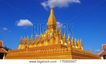 Golden Pagoda in Laos with blue sky.
