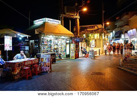 HERSONISSOS, CRETE - SEPTEMBER 18, 2016 - Henna tattoo stall and shops along a harbour shopping street at night Hersonissos Crete Greece Europe, September 18, 2016.