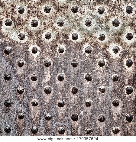 Rusty metal texture. Studded iron plate. Rivets on old rusty metal door. Weathered aged grunge texture.