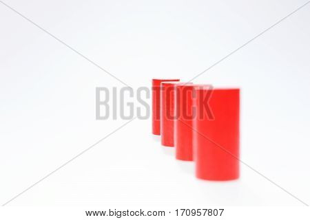 Four red round wooden building blocks in a row one behind the other