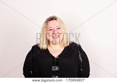 Portrait of a smiling fat woman in a black dress on a white background.