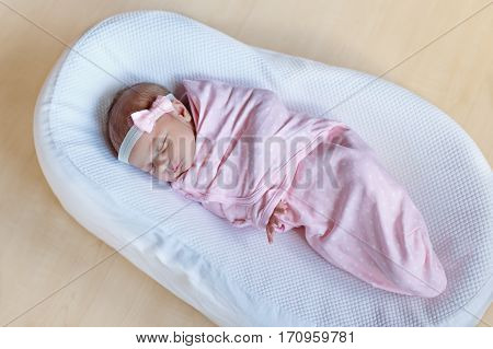 One week old adorable newborn baby wrapped in pink blanket and hairband sleeping. Closeup of cute peaceful child, little baby girl sleeping. Family, Birth, new life