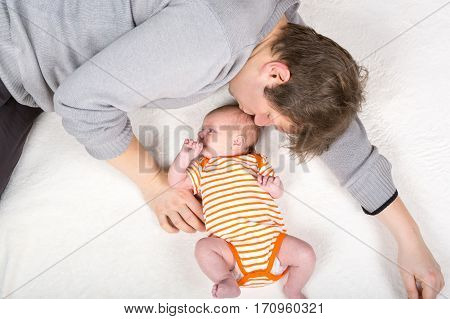 Happy proud young father with newborn baby daughter, family portrait togehter. Dad with baby girl, love. New born child looking on dad. Bonding, family, new life