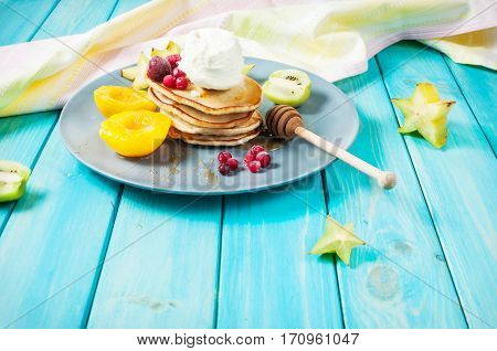 Pancakes with Vanilla Ice Cream on blue wood plate