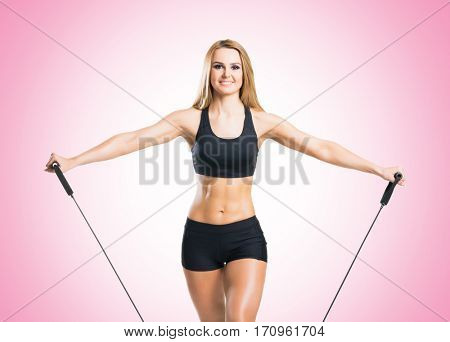 Fit, healthy and sporty woman in sportswear doing expander exercise pink background.